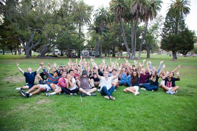 Sock Institute students put their hands in the air before handing out socks to street friends.
