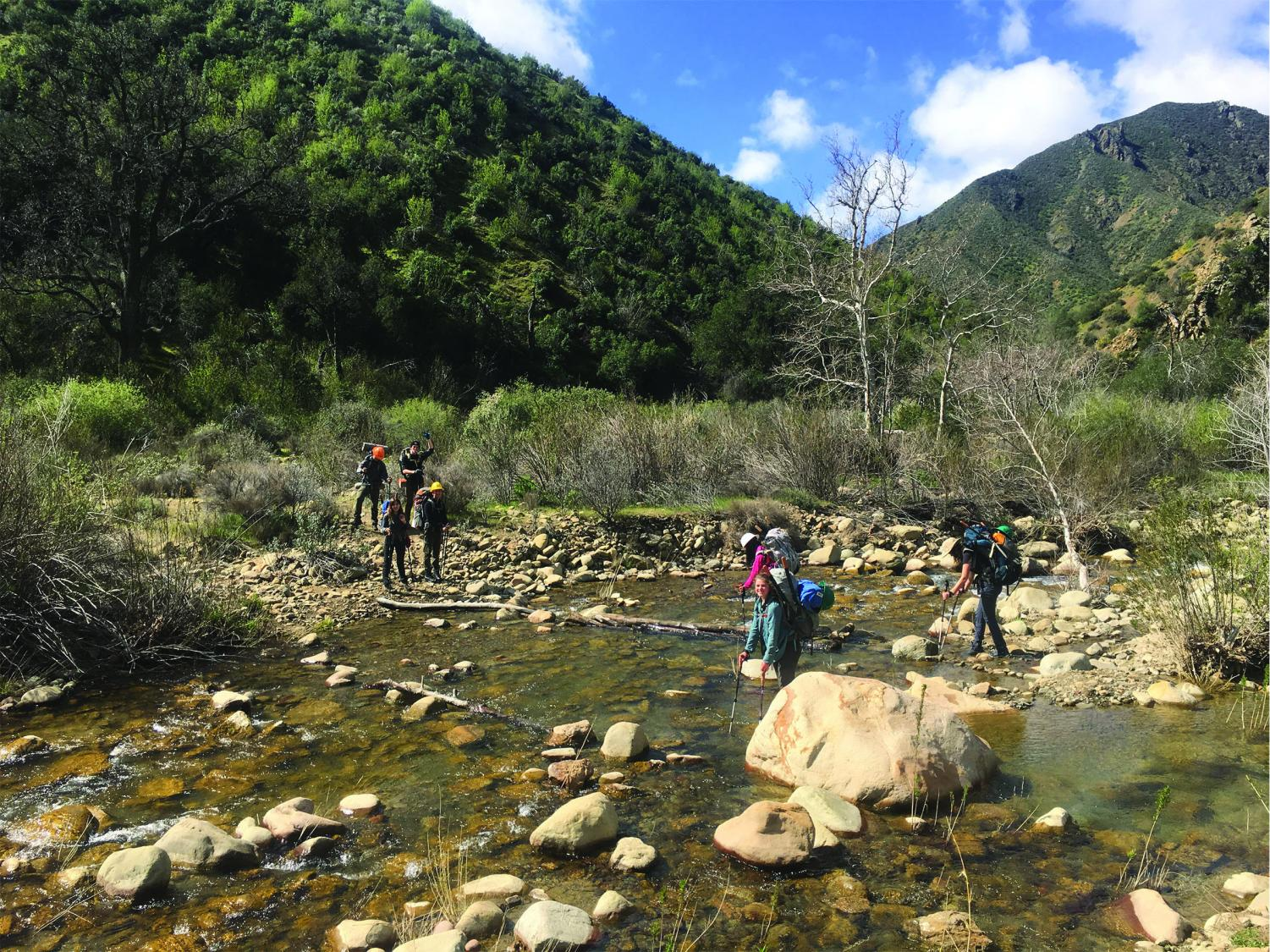 Students cross the creek while heading to camp